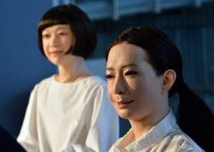 """The new humanoid robots named """"Otonaroid"""" (R) and """"Kodomoroid (R) are pictured during a press preview at the National Museum of Emerging Science and Technology in Tokyo on June 24, 2014.  Japanese scientists unveiled what they said was the world's first news-reading android, eerily lifelike and possessing a sense of humour to match her perfect language skills.    AFP PHOTO / Yoshikazu TSUNO        (Photo credit should read YOSHIKAZU TSUNO/AFP/Getty Images)"""